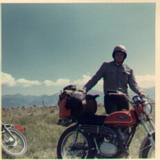 Image of me in riding gear and helmet, standing behind bike with backpack and sleeping bag bungeed to the back